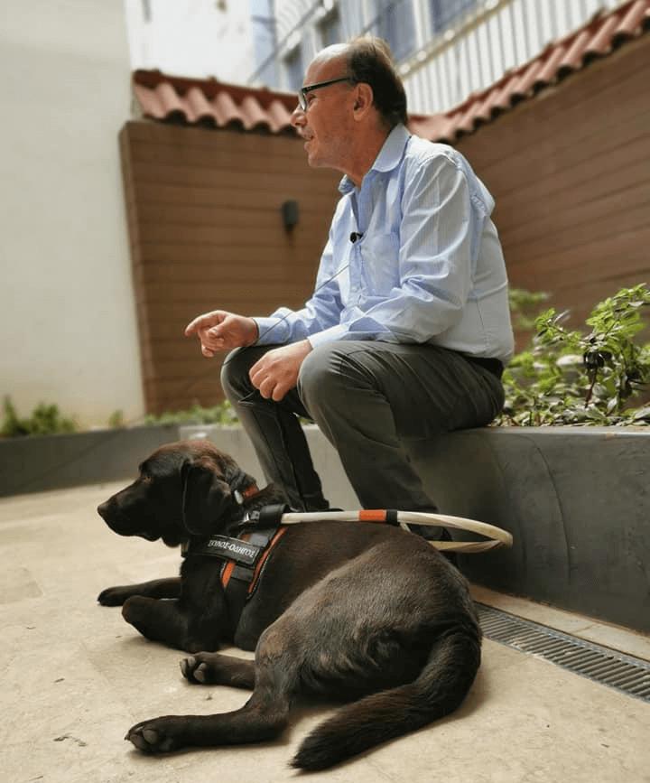 Άτομο με βλάβη στην όραση μαζί με τον σκύλο οδηγό του από τη Σχολή Λάρα